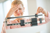 Doubtful mature woman adjusting weight scale at health club