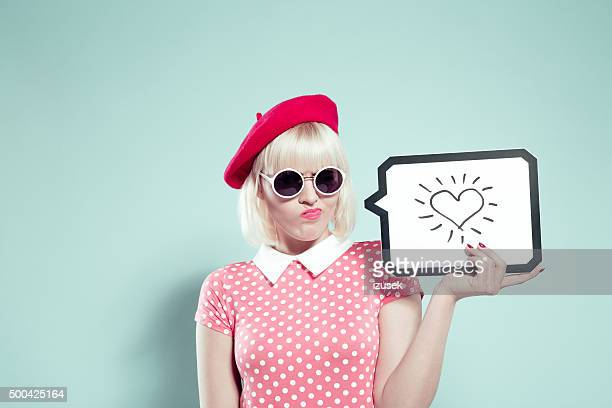 Doubtfully young woman holding speech bubble with drawn heart