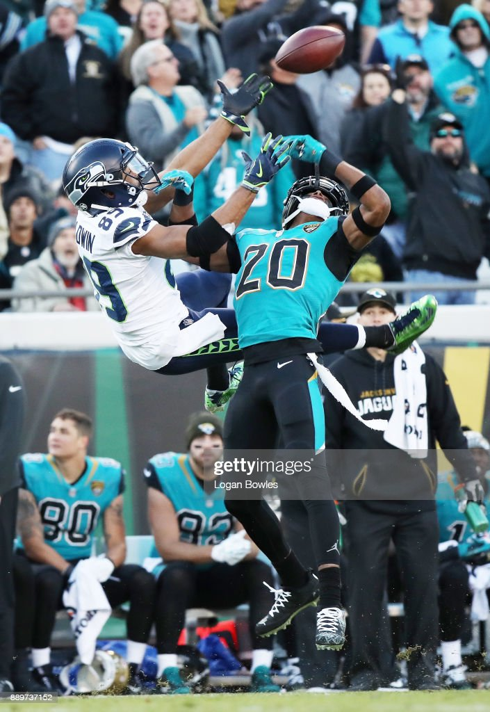 Doug Baldwin #89 of the Seattle Seahawks and Jalen Ramsey #20 of the Jacksonville Jaguars reach for the football during the first half of their game at EverBank Field on December 10, 2017 in Jacksonville, Florida.