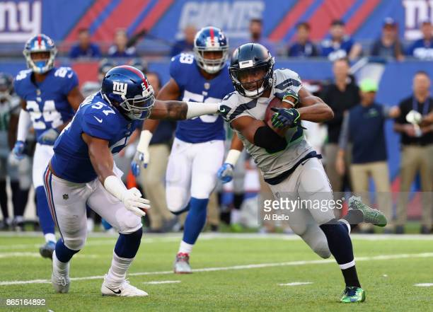 Doug Baldwin of the Seattle Seahawks runs the ball before being tackled by Keenan Robinson of the New York Giants during the first half of the game...