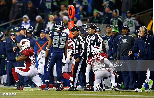 Doug Baldwin of the Seattle Seahawks talks to the referee after an interception by Carlos Dansby of the Arizona Cardinals as Yeremiah Bell celebrates...
