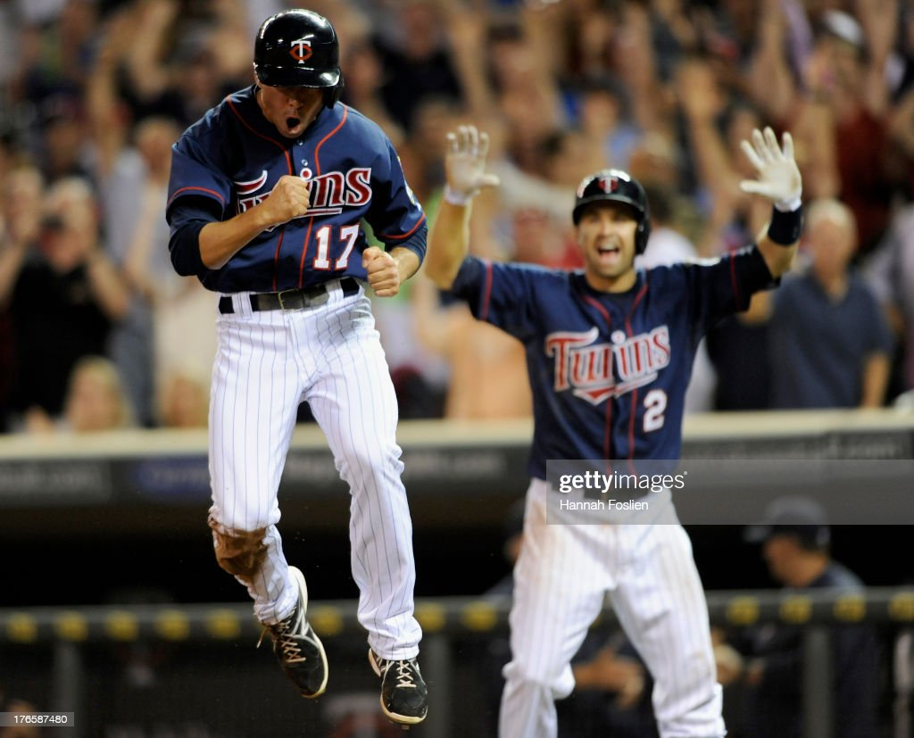 Doug Bernier #17 of the Minnesota Twins celebrates after scoring the winning run as teammate <a gi-track='captionPersonalityLinkClicked' href=/galleries/search?phrase=Brian+Dozier&family=editorial&specificpeople=7553002 ng-click='$event.stopPropagation()'>Brian Dozier</a> #2 looks on after the game against the Chicago White Sox on August 15, 2013 at Target Field in Minneapolis, Minnesota. The Twins defeated the White Sox 4-3.