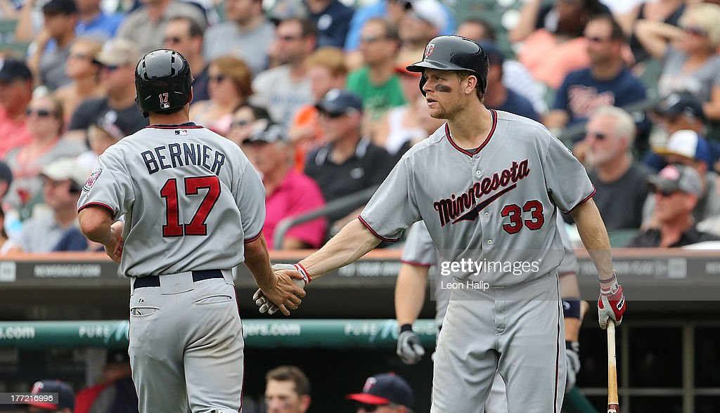 <a gi-track='captionPersonalityLinkClicked' href=/galleries/search?phrase=Doug+Bernier&family=editorial&specificpeople=5734598 ng-click='$event.stopPropagation()'>Doug Bernier</a> #17 of the Minnesota Twins is congratulated by <a gi-track='captionPersonalityLinkClicked' href=/galleries/search?phrase=Justin+Morneau&family=editorial&specificpeople=211556 ng-click='$event.stopPropagation()'>Justin Morneau</a> #33 after scoring on the double to right center field from <a gi-track='captionPersonalityLinkClicked' href=/galleries/search?phrase=Chris+Herrmann&family=editorial&specificpeople=7553012 ng-click='$event.stopPropagation()'>Chris Herrmann</a> #12 during the eighth inning of the game against the Detroit Tigers at Comerica Park on August 22, 2013 in Detroit, Michigan. The Twins defeated the Tigers 7-6.