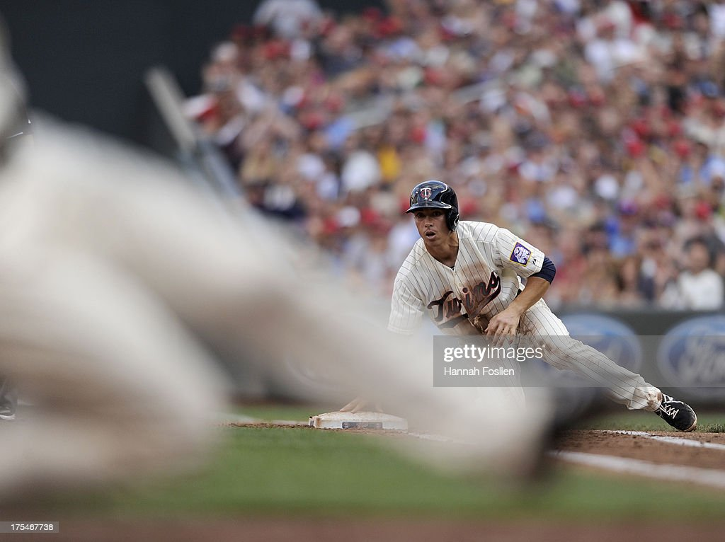 Doug Bernier #17 of the Minnesota Twins looks on from first base after escaping a rundown as teammate Clete Thomas #11 of the Minnesota Twins steals home plate during the second inning of the game against the Houston Astros on August 3, 2013 at Target Field in Minneapolis, Minnesota.