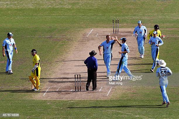 Doug Bollinger of the Blues celebrates with team mates after taking the wicket of Sam Whiteman of the Warriors during the Matador BBQs One Day Cup...