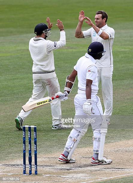 Doug Bracewell of New Zealand is congratulated on taking the wicket of Suranga Lakmal of Sri Lanka during day five of the First Test match between...