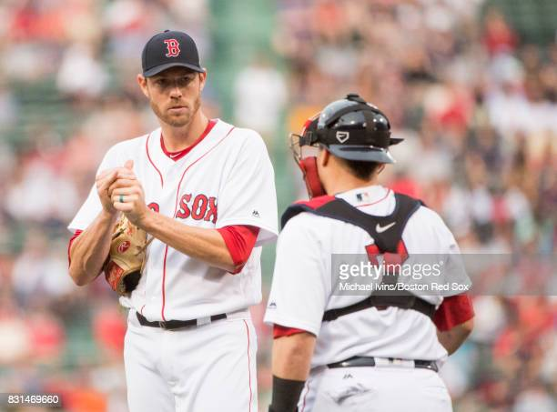Doug Fister of the Boston Red Sox talks with catcher Christian Vazquez after allowing the bases loaded against the Cleveland Indians in the second...