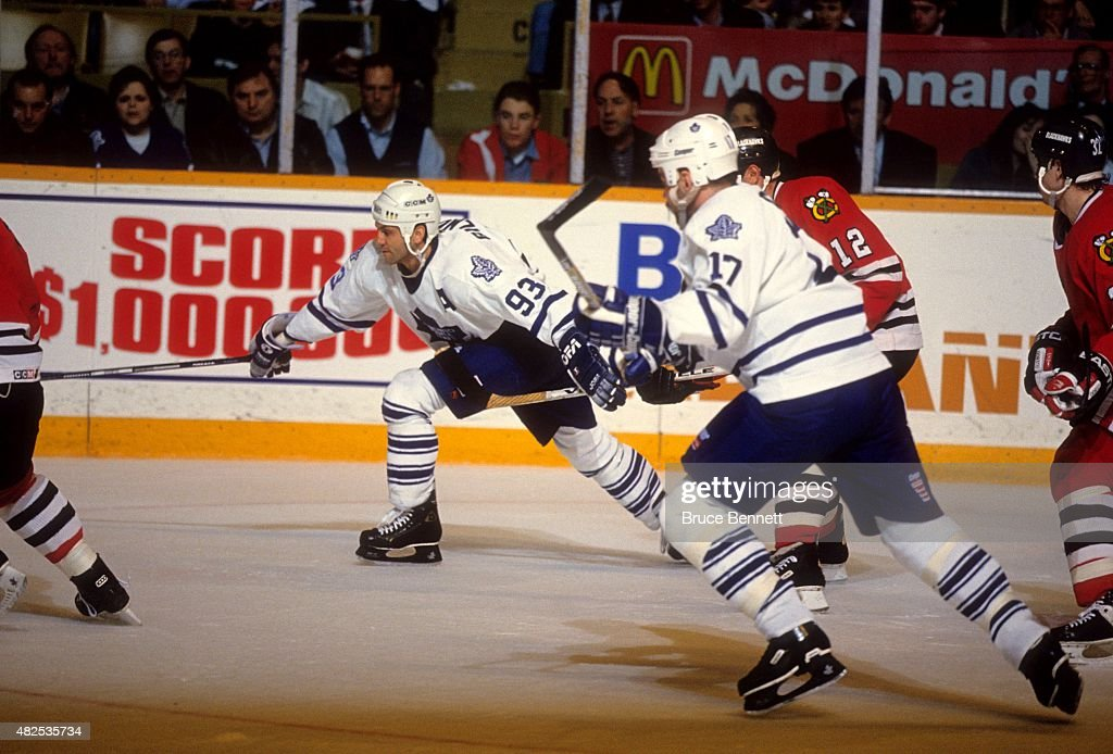 <a gi-track='captionPersonalityLinkClicked' href=/galleries/search?phrase=Doug+Gilmour&family=editorial&specificpeople=210813 ng-click='$event.stopPropagation()'>Doug Gilmour</a> #93 and <a gi-track='captionPersonalityLinkClicked' href=/galleries/search?phrase=Wendel+Clark&family=editorial&specificpeople=882632 ng-click='$event.stopPropagation()'>Wendel Clark</a> #17 of the Toronto Maple Leafs go for the puck during an NHL game against the Chicago Blackhawks on April 12, 1994 at the Maple Leaf Gardens in Toronto, Ontario, Canada.
