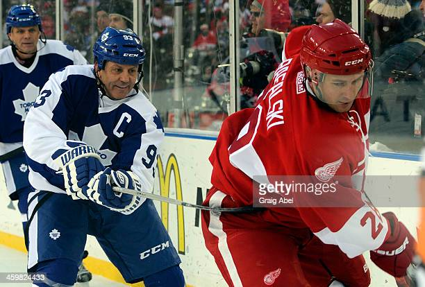 Doug Gilmour of the Toronto Maple Leafs Alumni hooks Brian Rafalski of the Detroit Red Wings Alumni during game action on December 31 2013 at...