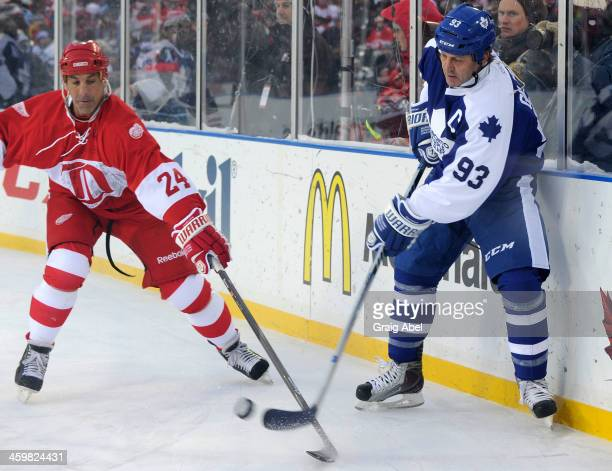 Doug Gilmour of the Toronto Maple Leafs Alumni puts the puck around Chris Chelios of the Detroit Red Wings Alumni during game action on December 31...