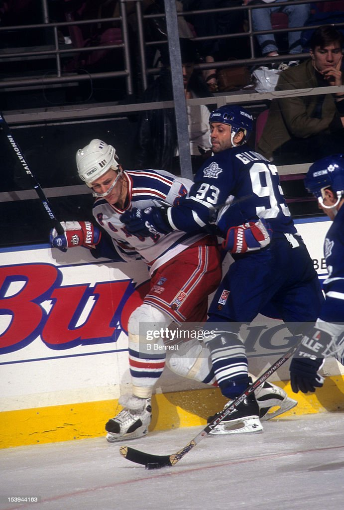 <a gi-track='captionPersonalityLinkClicked' href=/galleries/search?phrase=Doug+Gilmour&family=editorial&specificpeople=210813 ng-click='$event.stopPropagation()'>Doug Gilmour</a> #93 of the Toronto Maple Leafs checks Alex Kovalev #27 into the boards during an NHL game on December 6, 1996 at the Madison Square Garden in New York, New York.