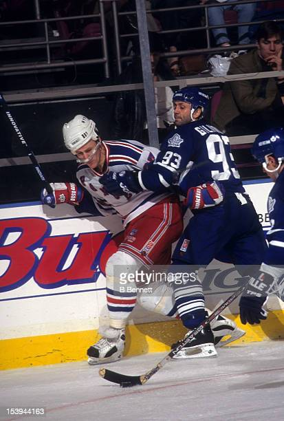 Doug Gilmour of the Toronto Maple Leafs checks Alex Kovalev into the boards during an NHL game on December 6 1996 at the Madison Square Garden in New...