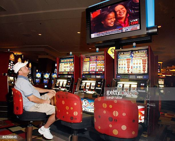 Doug Harvey of Missouri plays a slot machine at the Planet Hollywood Resort Casino as he watches a television screen broadcasting an image of Barack...