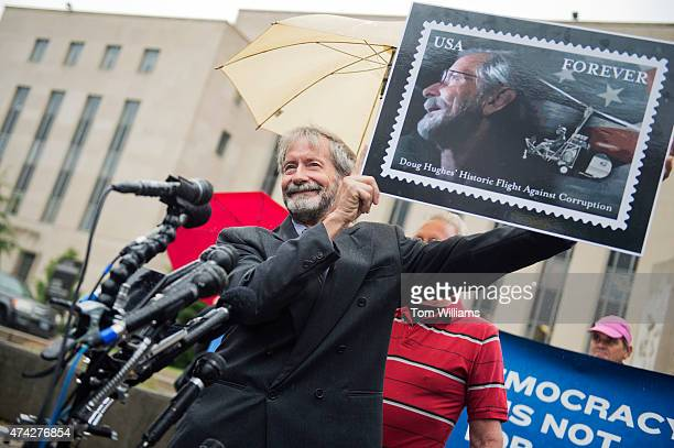 Doug Hughes holds a poster of a stamp made in likeness during a news conference outside of the E Barrett Prettyman Federal Courthouse May 21 after...