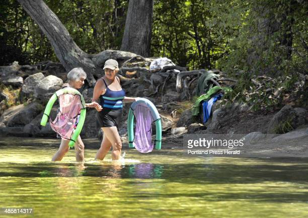 Doug Jones/Staff Photographer Sunday July 20 2009 Bonnie Deutch helps her mother Naomi Stitson ashore after their swim at the beach on Long Pond in...