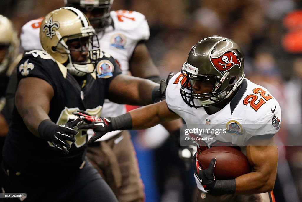 Doug Martin #22 of the Tampa Bay Buccaneers runs past Sedrick Ellis #98 of the New Orleans Saints at the Mercedes-Benz Superdome on December 16, 2012 in New Orleans, Louisiana.
