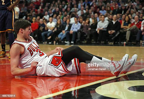 Doug McDermott of the Chicago Bulls grimaces after landing hard on the floor against the Indiana Pacers at the United Center on March 18 2015 in...
