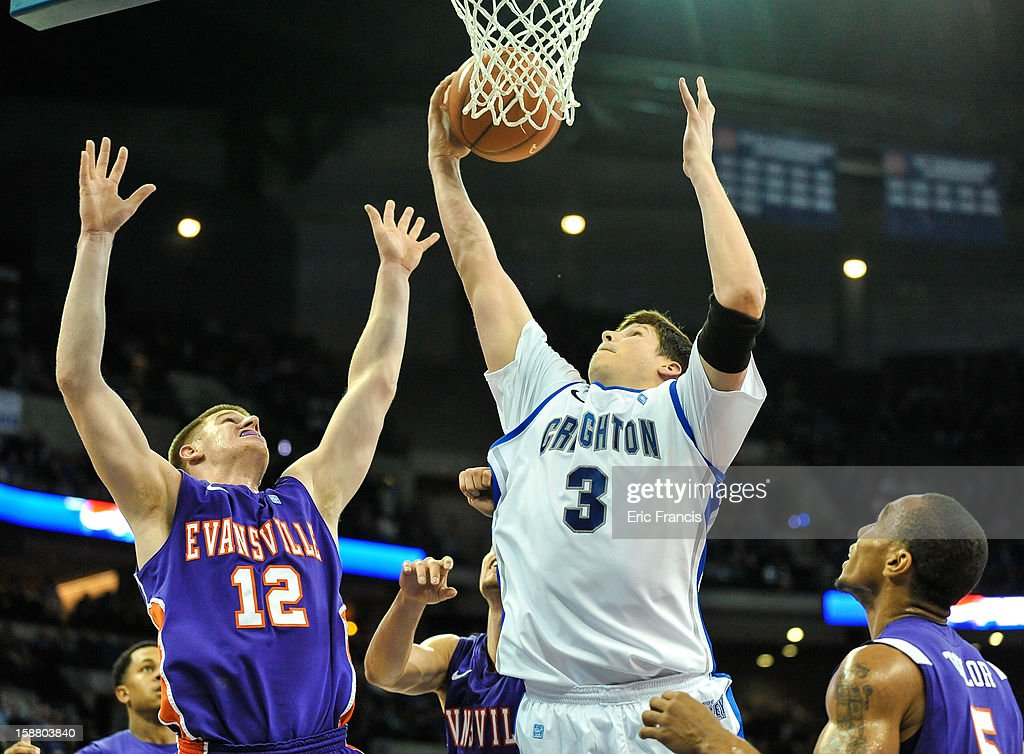 Doug McDermott #3 of the Creighton Bluejays pulls in a rebound over Adam Wing #12 and Troy Taylor #5 of the Evansville Aces during their game at the CenturyLink Center on December 29, 2012 in Omaha, Nebraska. Creighton defeated Evansville 87-70.