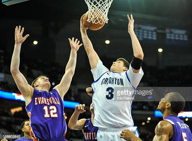 Doug McDermott of the Creighton Bluejays pulls in a rebound over Adam Wing and Troy Taylor of the Evansville Aces during their game at the...