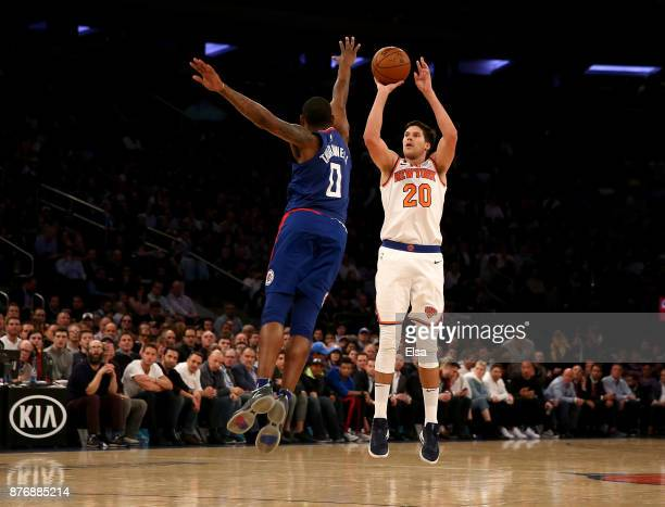 Doug McDermott of the New York Knicks shoots a three point shot as Sindarius Thornwell of the Los Angeles Clippers defends at Madison Square Garden...