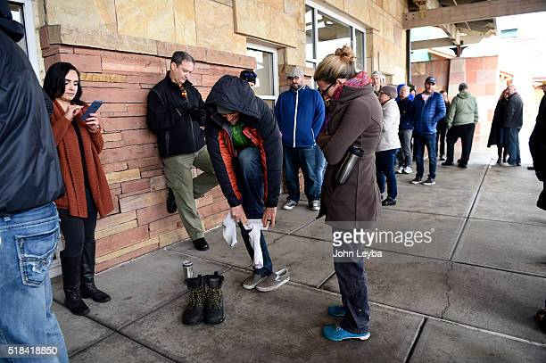 Doug Michaels 41 years old of Golden puts on warm socks and winter boots that were brought to him by his wife Elisabeth Michaels as he stands in line...