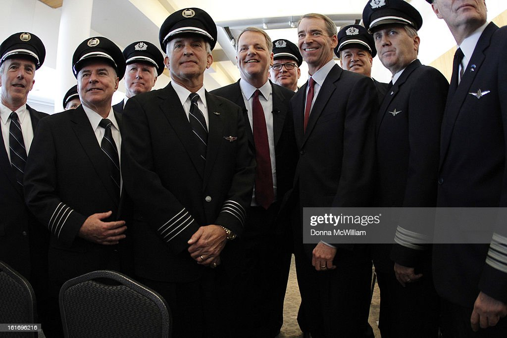Doug Parker (5th L), Chairman and CEO of US Airways, and Thomas Horton (4th R) , Chairman, President and Chief Executive Officer of American Airlines stand with pilots from both American Airlines and US Airways, during a news conference to announce the merger of the two airlines February 14, 2013 in Dallas Texas. US Airways and American Airlines have agreed to an $11 billion merger, creating the largest airline in the world. The airline will be called American Airlines and be headed by US Airways CEO Doug Parker. (Photo by Donna McWilliam/Getty Images