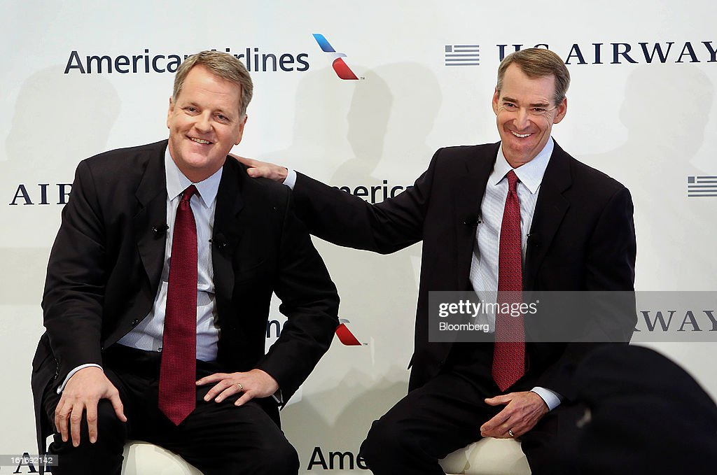Doug Parker, chief executive officer of US Airways Group Inc., left, and Tom Horton, president and chief executive officer of AMR Corp.'s American Airlines, smile during a press conference at Dallas Fort Worth Airport in Fort Worth, Texas,U.S., on Thursday, Feb. 14, 2013. US Airways Group Inc., spurned in three prior merger attempts, will combine with bankrupt AMR Corp.'s American Airlines in an $11 billion all-stock deal to create the world's largest carrier. Photographer: Mike Fuentes/Bloomberg via Getty Images