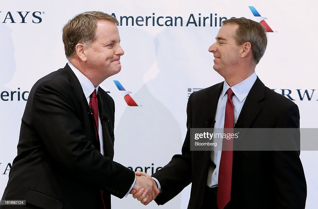 Doug Parker, chief executive officer of US Airways Group Inc., left, shakes hands with Tom Horton, president and chief executive officer of AMR Corp.'s American Airlines, during a press conference at Dallas Fort Worth Airport in Fort Worth, Texas,U.S., on Thursday, Feb. 14, 2013. US Airways Group Inc., spurned in three prior merger attempts, will combine with bankrupt AMR Corp.'s American Airlines in an $11 billion all-stock deal to create the world's largest carrier. Photographer: Mike Fuentes/Bloomberg via Getty Images