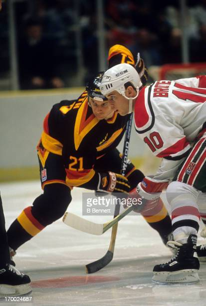Doug Smith of the Vancouver Canucks takes the faceoff against Aaron Broten of the New Jersey Devils on March 20 1989 at the Brendan Byrne Arena in...
