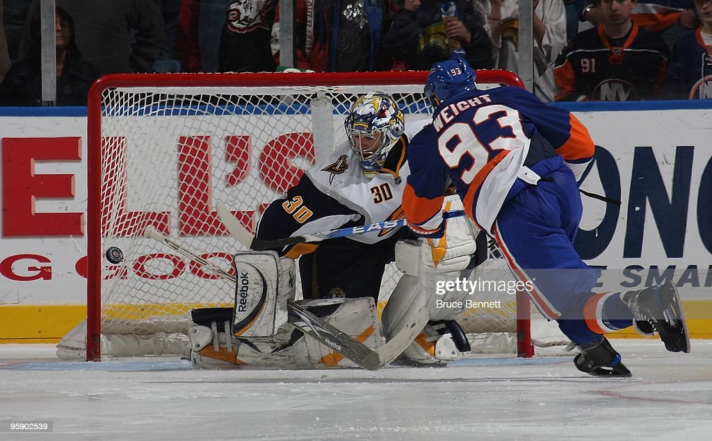 Doug Weight of the New York Islanders misses the net during a shoot out attempt against Ryan Miller of the Buffalo Sbares at the Nassau Coliseum on...
