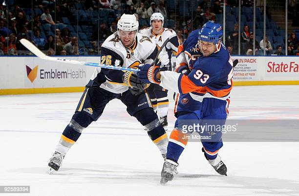 Doug Weight of the New York Islanders shoots the puck against Thomas Vanek of the Buffalo Sabres on October 31 2009 at Nassau Coliseum in Uniondale...