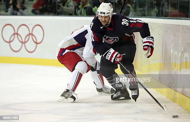 Doug Weight of the United States controls thepuck against the defense of Russia during the men's ice hockey Preliminary Round Group B match during...