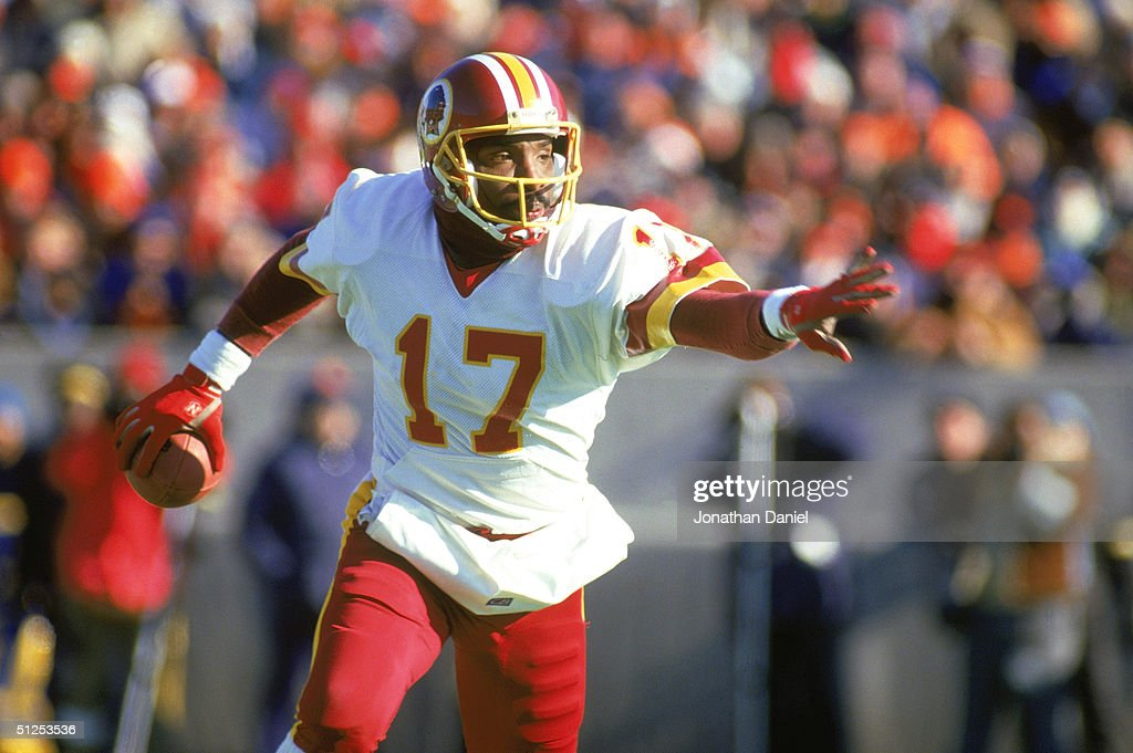 Doug Williams of the Washington Redskins scrambles with the ball during a 1987 NFL season game