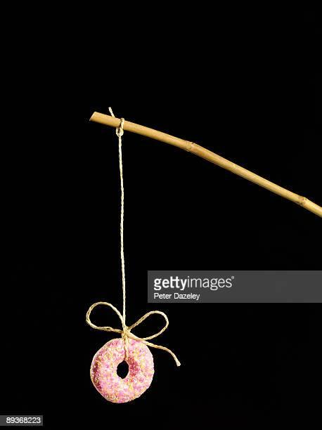 Doughnut on stick on black background.