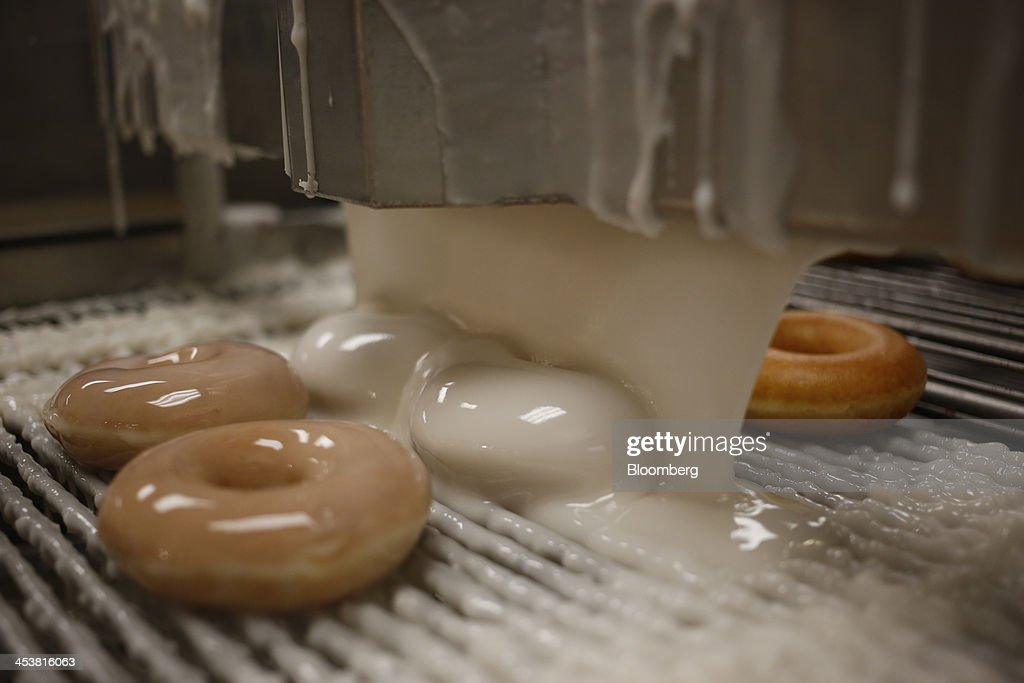 Doughnuts are glazed on an assembly line at a Krispy Kreme Doughnuts Inc. store in Farragut, Tennessee, U.S., on Wednesday, Dec. 5, 2013. The doughnut chain plans to add at least 30 new U.S. stores next year and is opening up new markets for franchising. Photographer: Luke Sharrett/Bloomberg via Getty Images