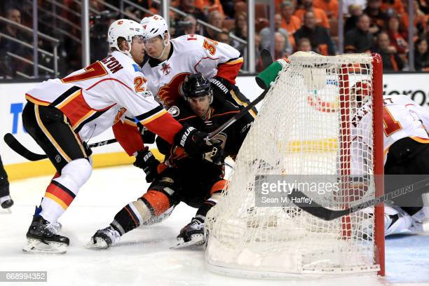 Dougie Hamilton and Alex Chiasson of the Calgary Flames defend against Andrew Cogliano of the Anaheim Ducks during the third period of Game Two of...