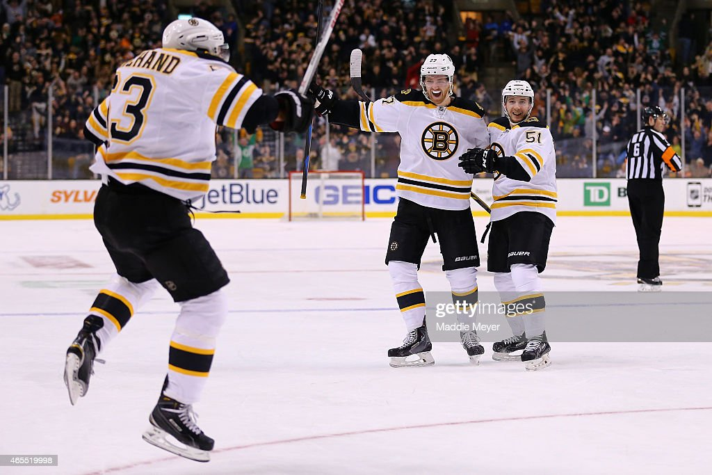 Dougie Hamilton and Ryan Spooner congratulate Brad Marchand of the Boston Bruins after he scored a goal in the third period against the Philadelphia...