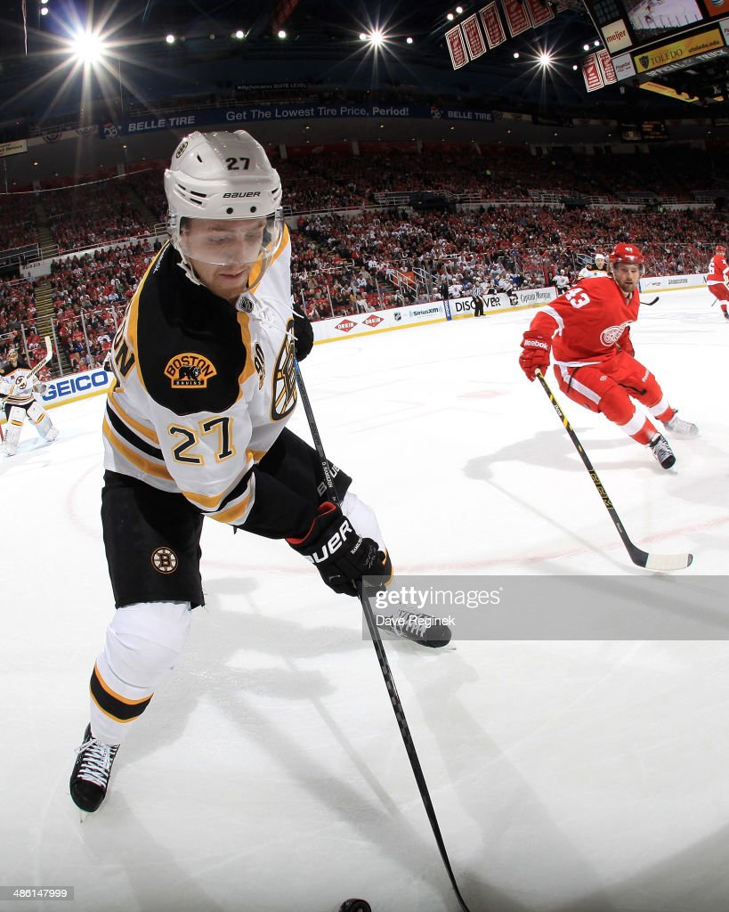 Dougie Hamilton #27 of the Boston Bruins digs the puck out of the corner as Darren Helm #43 of the Detroit Red Wings pressure him during Game Three of the First Round of the 2014 Stanley Cup Playoffs on April 22, 2014 at Joe Louis Arena in Detroit, Michigan.
