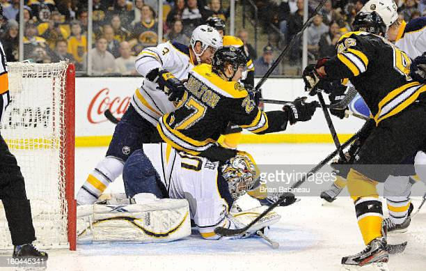 Dougie Hamilton of the Boston Bruins gets checked against by Jordan Leopold of the Buffalo Sabres at the TD Garden on January 31 2013 in Boston...