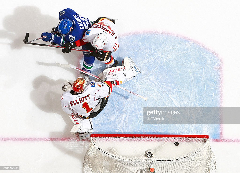 Dougie Hamilton #27 of the Calgary Flames and Brendan Gaunce #50 of the Vancouver Canucks watch as a shot from Markus Granlund #60 of the Vancouver Canucks gets past goaltender Brian Elliott #1 of the Calgary Flames for a Vancouver goal during their NHL game at Rogers Arena January 6, 2017 in Vancouver, British Columbia, Canada. Vancouver won 4-2.