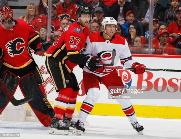 Dougie Hamilton of the Calgary Flames battles against Victor Rask of the Carolina Hurricanes at Scotiabank Saddledome on October 19 2017 in Calgary...
