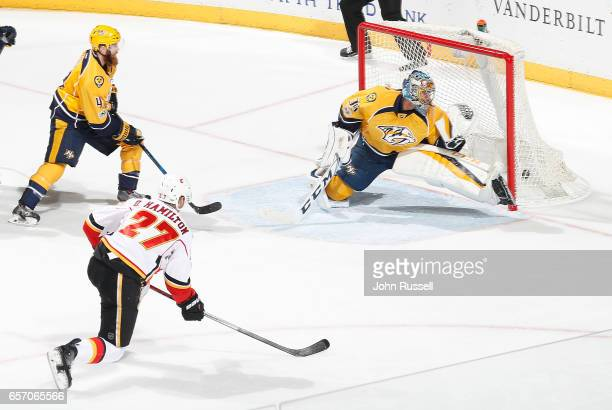 Dougie Hamilton of the Calgary Flames beats Pekka Rinne of the Nashville Predators for a goal during an NHL game at Bridgestone Arena on March 23...