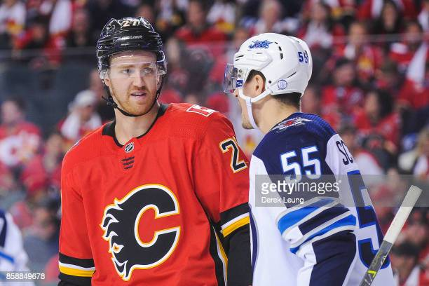 Dougie Hamilton of the Calgary Flames confers with Mark Scheifele of the Winnipeg Jets during an NHL game at Scotiabank Saddledome on October 7 2017...