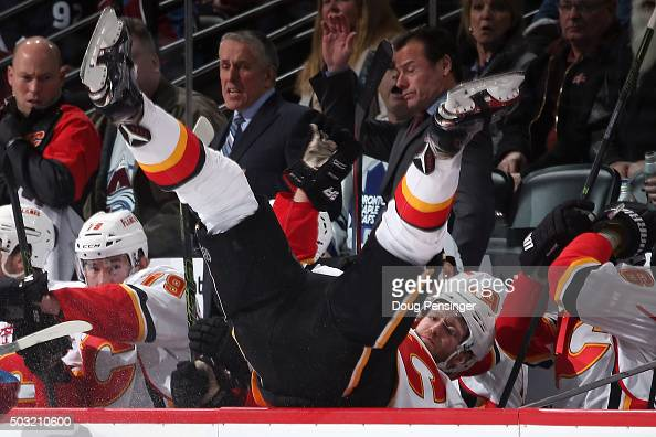 Dougie Hamilton of the Calgary Flames is checked into his bench by Erik Johnson of the Colorado Avalanche in the second period at Pepsi Center on...