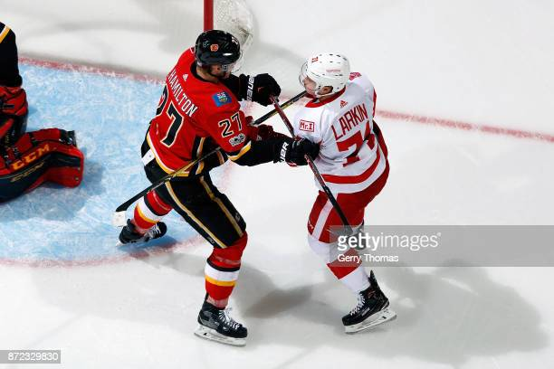 Dougie Hamilton of the Calgary Flames skates against Dylan Larkin of the Detroit Red Wings during an NHL game on November 9 2017 at the Scotiabank...