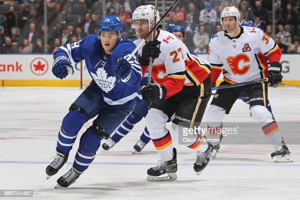Dougie Hamilton of the Calgary Flames skates against William Nylander of the Toronto Maple Leafs during an NHL game at the Air Canada Centre on...