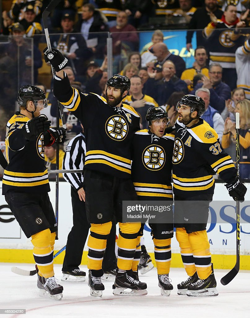 Dougie Hamilton #27, Zdeno Chara #33, and Patrice Bergeron #37 congratulate Brad Marchand #63 of the Boston Bruins after he scored a goal against the Calgary Flames during the first period at TD Garden on March 5, 2015 in Boston, Massachusetts.
