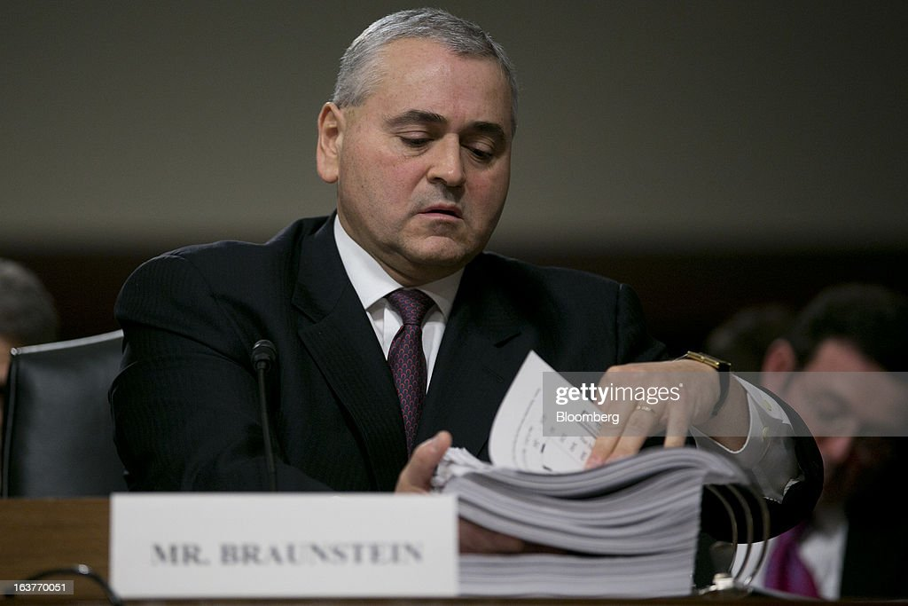 Douglas Braunstein, vice chairman of JPMorgan Chase & Co., looks through an exhibits binder during a Senate Permanent Subcommittee on Investigations hearing in Washington, D.C., U.S., on Friday, March 15, 2013. JPMorgan Chase, the biggest U.S. bank by assets, compensated chief investment office traders in a way that encouraged risk-taking before the unit amassed losses exceeding $6.2 billion, a Senate committee said. Photographer: Andrew Harrer/Bloomberg via Getty Images