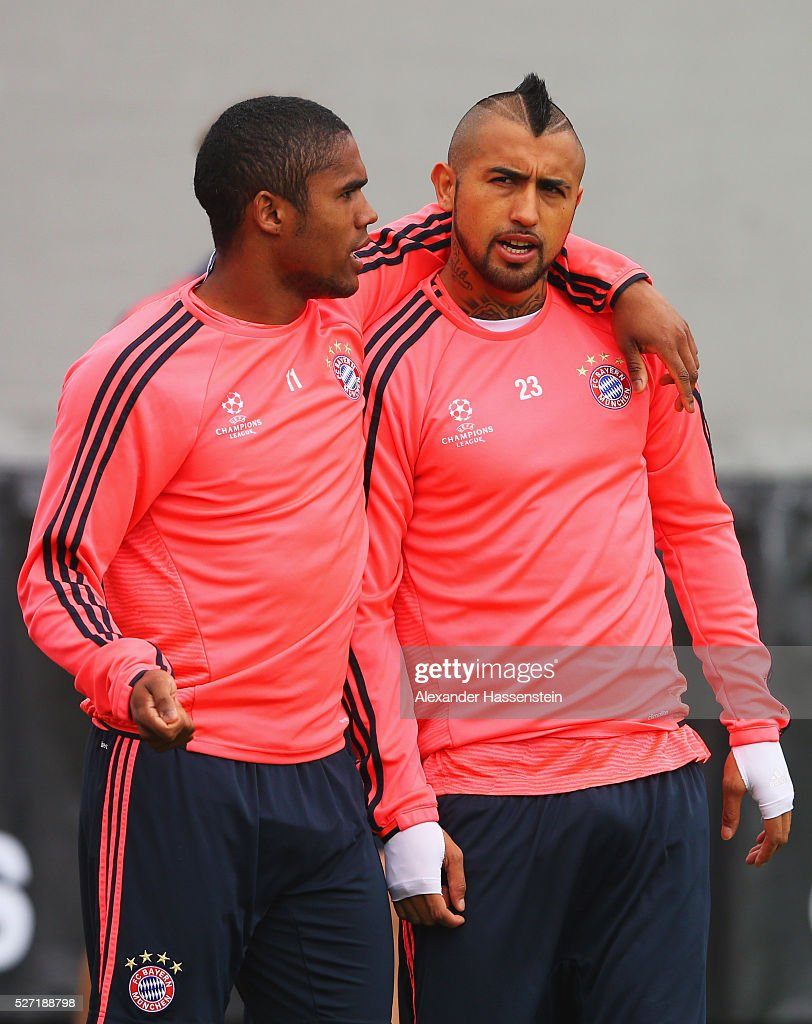 Douglas Costa (L) and Arturo Vidal in discussion during a FC Bayern Muenchen training session ahead of their UEFA Champions League semi final second leg match against Club Atletico de Madrid at the Saebener Strasse training ground on May 2, 2016 in Munich, Germany.