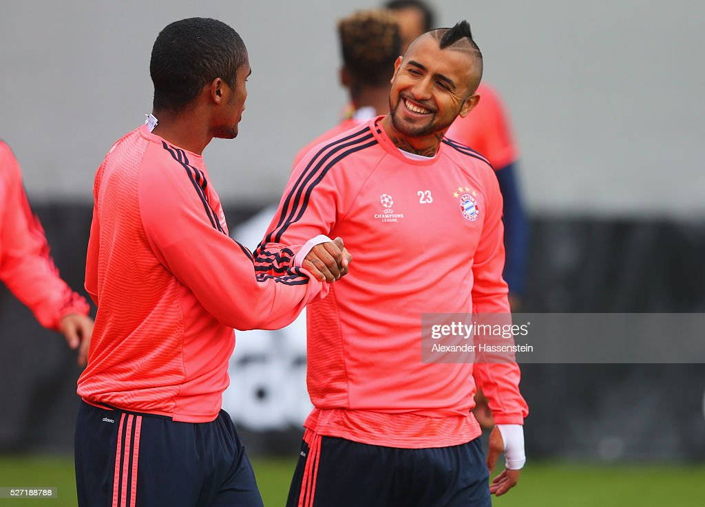 Douglas Costa (L) and Arturo Vidal shake hands during a FC Bayern Muenchen training session ahead of their UEFA Champions League semi final second leg match against Club Atletico de Madrid at the Saebener Strasse training ground on May 2, 2016 in Munich, Germany.